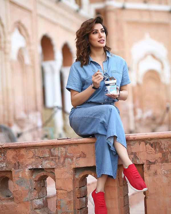 Mehwish Hayat posing with a cup in her hand